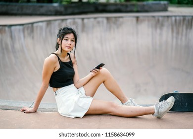 Portrait of a young Chinese Asian millennial skater girl checking her smartphone as she takes a break with her skateboard in the skate park. The teenager is cute, pretty and dressed for skating.