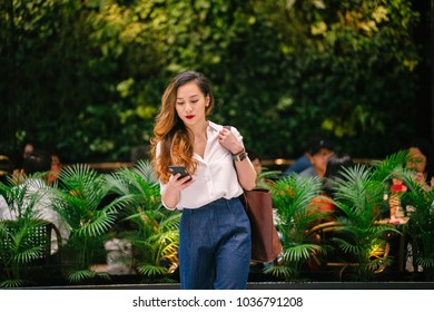 Portrait of a young Chinese Asian (Singaporean) woman walking in the city. She is fashionably dressed and might be a professional (lawyer, banker) or influencer blogger. She