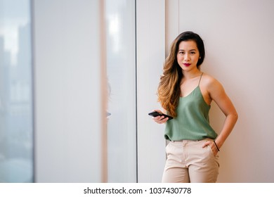 Portrait of a young Chinese Asian (Singaporean) woman using her mobile phone in the day. She is fashionably dressed in a green top and khaki pants and smiling.
