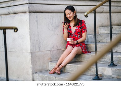 Portrait of a young Chinese Asian woman checking her smartphone as she sits on steps during the day. She is wearing a casual red summer dress. She is also smiling happily.