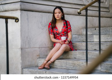 Portrait of a young Chinese Asian woman in a red dress sitting on the steps of a library or court house. She is holding a hot cup of coffee and is waiting for someone.