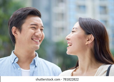 portrait of young Chinese couple standing & smiling at each other outdoor in garden