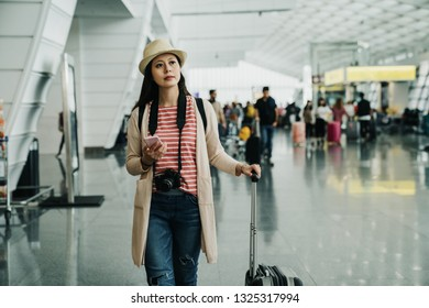 Portrait of young chinese girl walking with suitcase and looking at mobile phone at airport lobby. beautiful lady photographer carrying camera while travel finding friend pick her up after arrival.