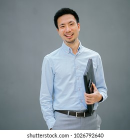 Portrait of a young, Chinese, Pan Asian business man standing against a plain grey background and smiling while he holds his leather folio. He is well-dressed in business casual and looks relaxed.