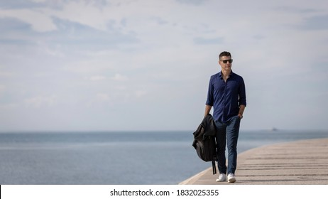 Portrait of a young classy entrepreneur relaxing alone along the Lisbon riverside in Portugal. Classy business man wearing a blue elegant shirt and formal outfit. Successful lifestyle concept.