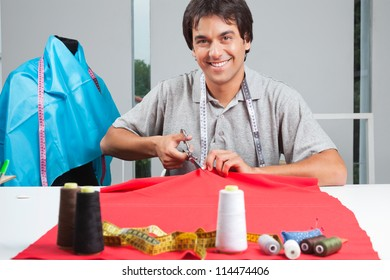 Portrait of young clothing dressmaker cutting red fabric with polyester threads on cloth