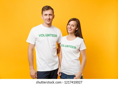 Portrait of young colleagues couple in white t-shirt with written inscription green title volunteer isolated on yellow background. Voluntary free work, assistance help, charity grace teamwork concept
