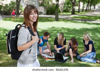 Portrait of young college girl at college campus with classmates studying in background