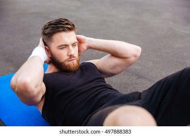 Portrait of a young concentrated handsome sports man doing press workout on fitness mat outdoors