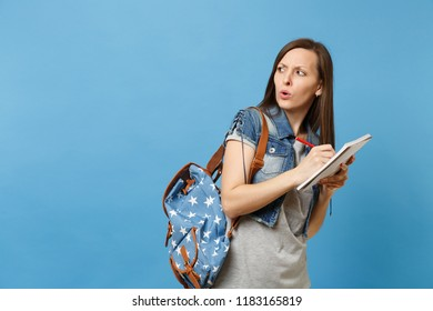 Portrait of young concerned doubtful woman student in grey t-shirt, denim clothes with backpack look aside writing on notebook isolated on blue background. Education in high school university college