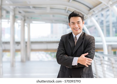 Portrait of young confident Asian businessman with arm crossed standing in city outdoor.