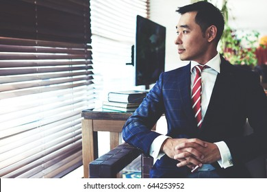 Portrait of young confident asian businessman with serious face sitting in modern office interior near big window, intelligent men entrepreneur in elegant suit thinking about something before meeting