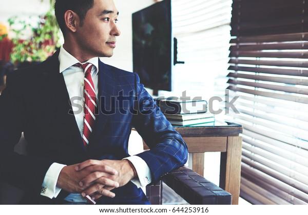 大きな窓の近くに現代のオフィスの内装に真面目な顔をした若い自信のあるアジアのビジネスマンのポートレート、出会う前に何かを思い浮かべたエレガントなスーツを着た知的な男性起業家