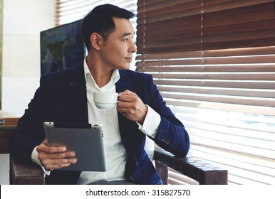 Portrait of young confident businessman enjoying coffee while work on his digital tablet in office space interior, thoughtful asian man in elegant suit holding touch pad while relaxing in modern cafe