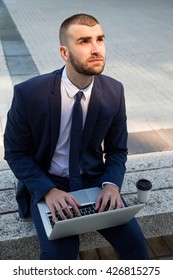 Portrait of a young confident businessman working with laptop computer outdoors. Looking away