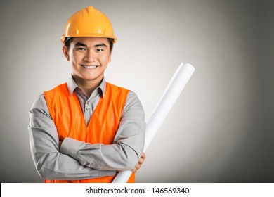 Portrait of a young confident engineer isolated on grey