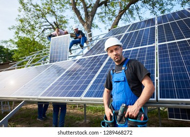 Portrait of young confident engineer technician with electrical screwdriver standing in front of unfinished high exterior solar panel photo voltaic system with team of workers on high platform.