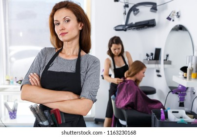 Portrait of young confident hairstylist standing in modern hair salon
