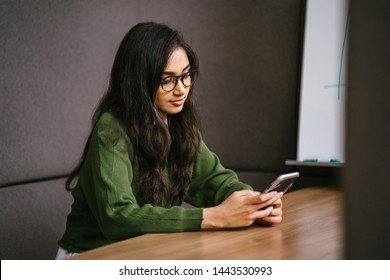 Portrait of a young, confident, intelligent-looking and attractive Indian Asian graduate student. She is smiling as she checks her smartphone. She is sitting in a study booth on her campus.