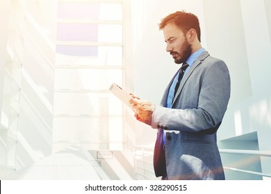 Portrait of young confident man economist holding digital tablet while standing in modern office corridor, male managing director dressed in luxury corporate clothes working on touch pad during break