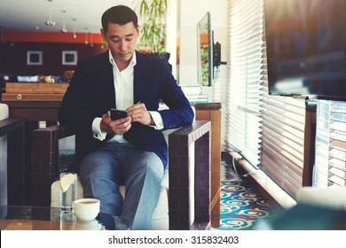 Portrait of young confident men entrepreneur dressed in luxury suit chatting on cell telephone during work break, intelligent male using his mobile phone while preparing for business meeting in office
