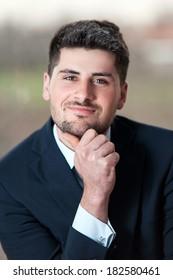 Portrait of a young confident successful smiling businessman in black suit