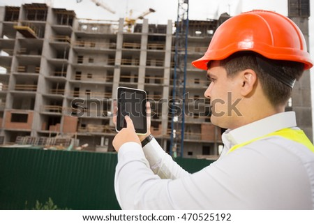 Portrait of young construction engineer using digital tablet on building site