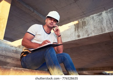 portrait of a young construction worker using mobile phone. Young man construction worker reading on clipboard while holding mobile phone.