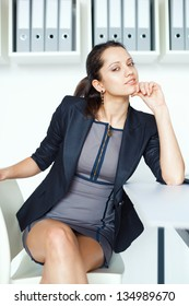 Portrait of young contemplative business woman sitting at the desk in office