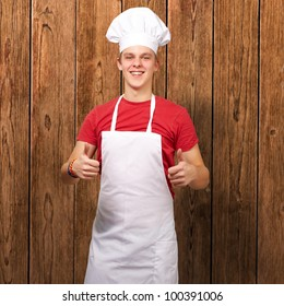 portrait of a young cook man doing a success symbol against a wooden wall