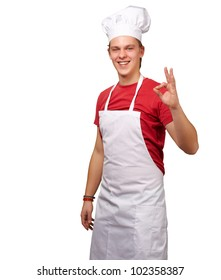 portrait of a young cook man doing a success symbol against a white background