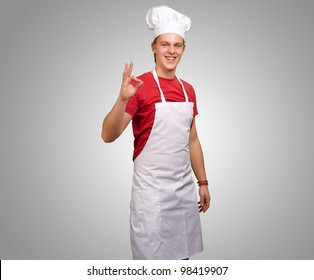 portrait of a young cook man doing a success symbol against a grey background