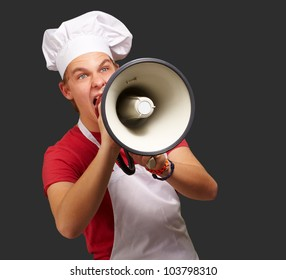 portrait of a young cook man screaming with a megaphone over a black background