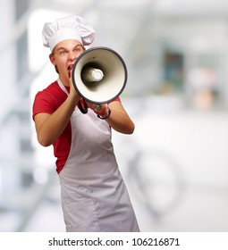 portrait of a young cook man screaming with a megaphone indoor