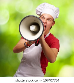 portrait of a young cook man screaming with a megaphone against a nature background