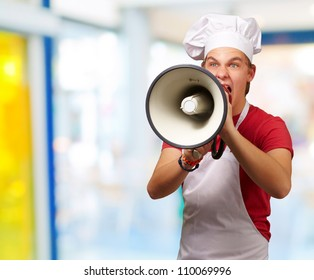 portrait of young cook man screaming with megaphone indoor