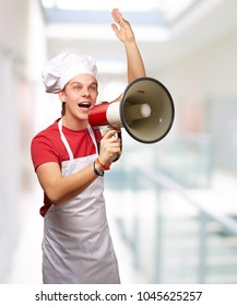 portrait of young cook man shouting with megaphone at modern building