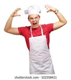 portrait of a young cook man wearing an apron doing an aggressive gesture over a white background