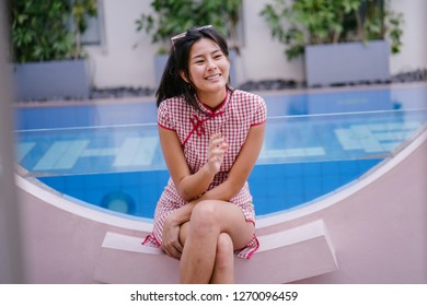 Portrait of a young and cool Asian Chinese woman wearing a traditional Qipao / Cheongsam dress with white sneakers. She is sitting by a pool at a resort during the day and smiling.