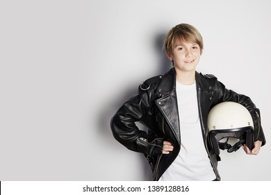 Portrait of Young cool beautiful teen kid in black leather jacket and holding hand white moto helmet smiling on white background