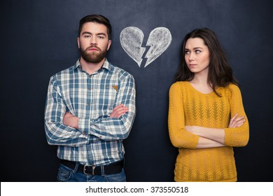Portrait of young couple after argument standing separately with hands folded over blackboard background