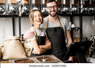 Portrait of a young couple of baristas standing together at the counter of the coffee store