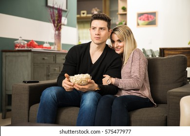 Portrait of a young couple cuddling and looking scared while watching a horror movie on TV at home