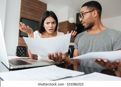 Portrait of a young couple discussing about domestic bills at home while looking at documents.