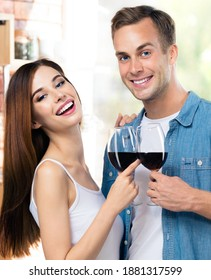 Portrait of young couple drinking redwine, at home. Caucasian models with red wine glasses in love concept. Happy man and woman posing together indoors.