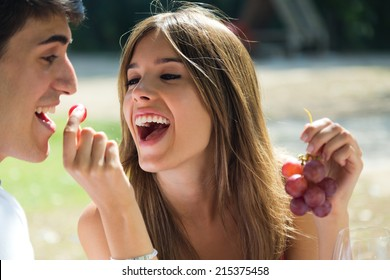 Portrait of young couple eating grapes on romantic picnic in countryside.