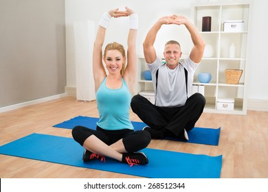 Portrait Of Young Couple Exercising Sitting On Mat