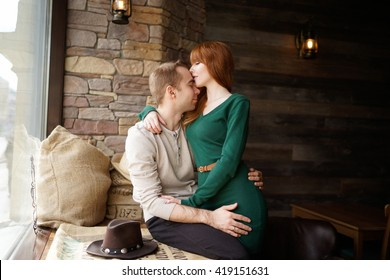 Portrait of young couple with eyes closed hugging on window sill in cafe