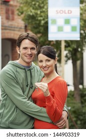 Portrait of young couple in front of new home with sold sign