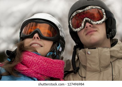 Portrait of young couple in helmets and gogles looking up